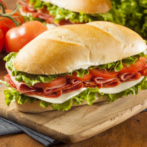 """Ham, pepperoni, salami, lettuce, tomato, red onion and provolone cheese, served with our own olive oil dressing and peperoncino. On 8"""" ciabatta bread."""