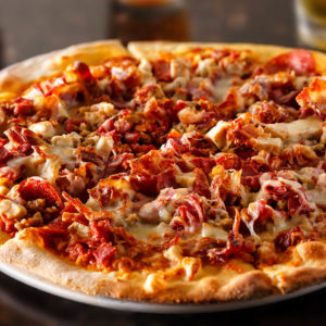 Red sauce, mozzarella cheese, pepperoni, ham, Italian sausage, Canadian bacon and bacon. Any specialty pizza can be made cheese less.