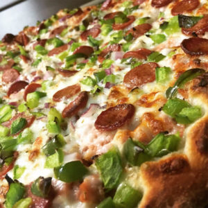 White sauce, pepperoni, ham, hot dog, mushrooms, black olives, green bell pepper, and tomatoes. Any specialty pizza can be made cheese less.
